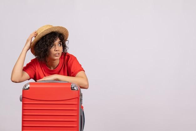 Vue de face jeune femme avec sac rouge se préparant au voyage sur fond blanc couleur soleil voyage reste vol touristique avion de vacances