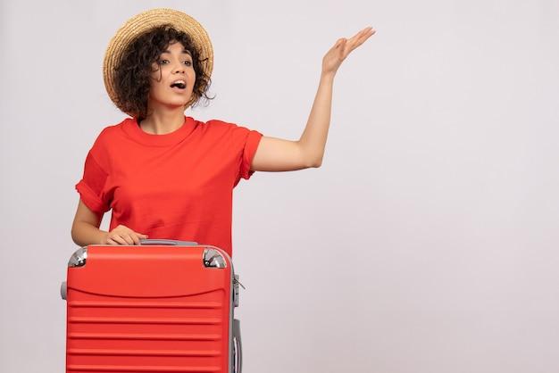 Vue de face jeune femme avec sac rouge se préparant au voyage sur fond blanc couleur de vol avion reste soleil voyage touristique vacances