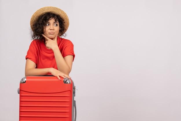 Vue de face jeune femme avec sac rouge se préparant au voyage sur fond blanc couleurs de vol avion reste soleil voyage vacances vacances