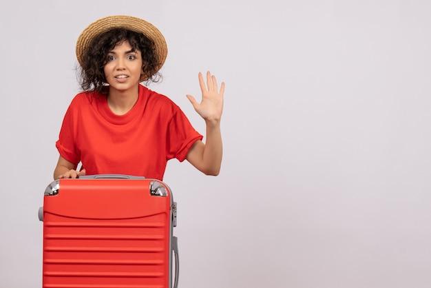 Vue de face jeune femme avec sac rouge se préparant au voyage sur fond blanc vacances couleur soleil voyage reste avion de vol touristique