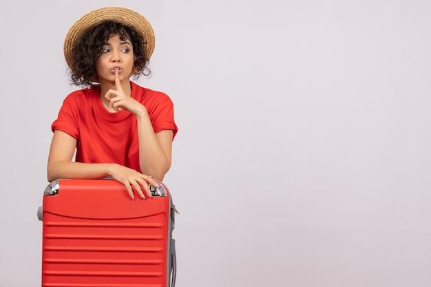 Vue de face jeune femme avec sac rouge se préparant au voyage sur fond blanc vacances de repos couleur soleil voyage en avion de vol touristique