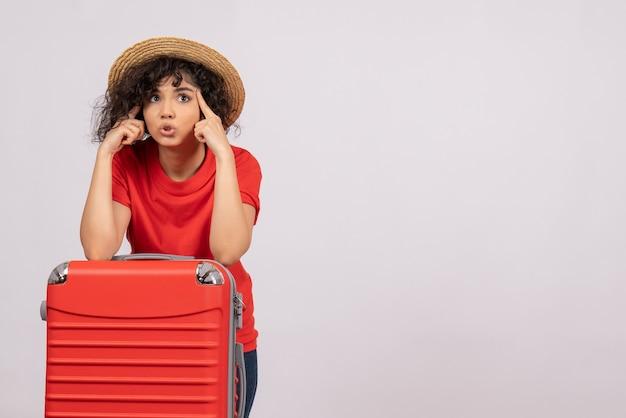 Vue de face jeune femme avec sac rouge se préparant au voyage sur fond blanc vacances de repos couleur voyage en avion de vol touristique