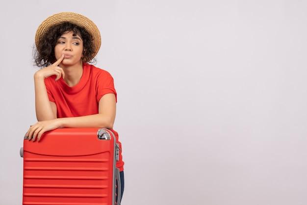 Vue de face jeune femme avec sac rouge se préparant au voyage sur fond blanc vacances de repos couleurs soleil vol touristique voyage en avion