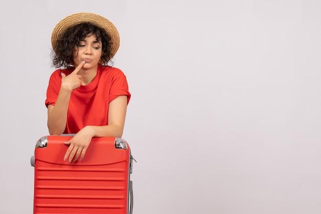 Vue de face jeune femme avec sac rouge se préparant au voyage sur fond blanc voyage vol couleur avion repos soleil vacances touristiques