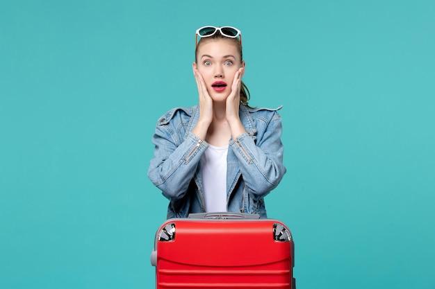 Vue de face jeune femme avec sac rouge se préparant pour des vacances sur l'espace bleu clair