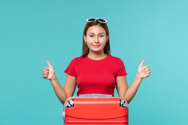 Vue de face jeune femme avec sac rouge se préparant pour des vacances sur l'espace bleu