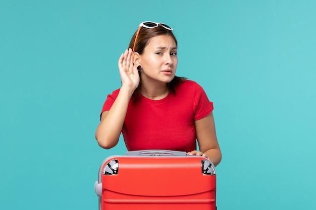 Vue de face jeune femme avec sac rouge se préparant pour les vacances en essayant d'entendre sur l'espace bleu