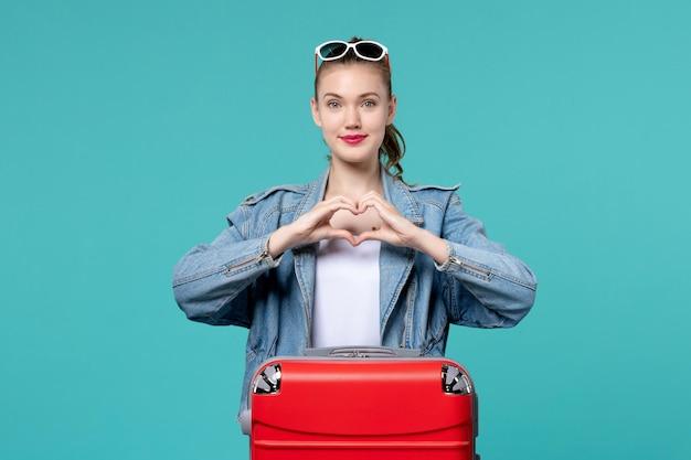 Vue de face jeune femme avec sac rouge se préparant pour les vacances et montrant un signe d'amour sur l'espace bleu