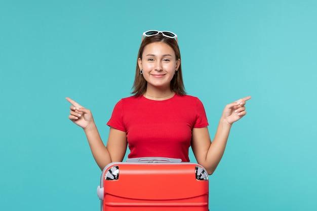 Vue de face jeune femme avec sac rouge se préparant pour les vacances en souriant sur l'espace bleu