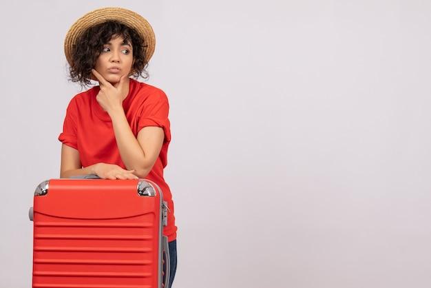 Vue de face jeune femme avec sac rouge se préparant pour un voyage sur un fond blanc avion reste vacances couleur soleil voyage de vol touristique