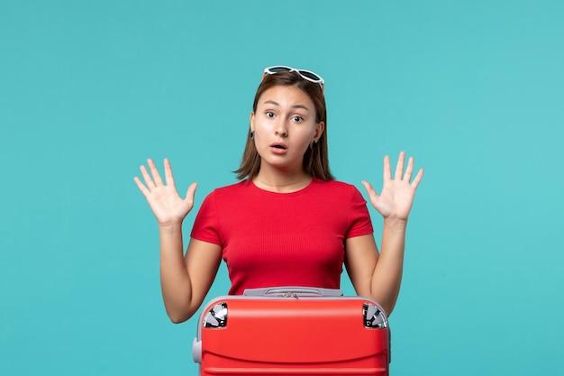 Vue de face jeune femme avec sac rouge se prépare pour les vacances sur le bureau bleu