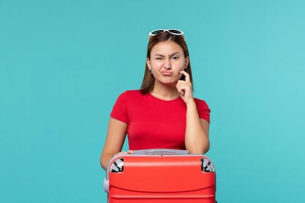 Vue de face jeune femme avec sac rouge se prépare pour les vacances sur l'espace bleu