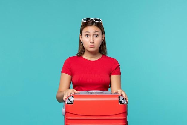 Vue de face jeune femme avec sac rouge se prépare pour les vacances avec une expression surprise sur l'espace bleu