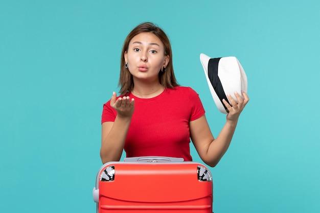 Vue de face jeune femme avec sac rouge tenant son chapeau sur l'espace bleu clair