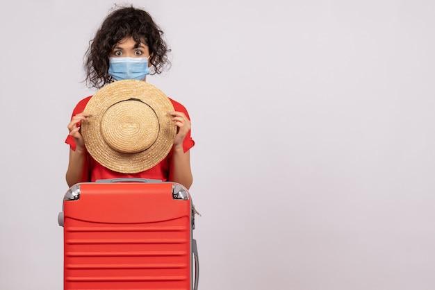 Vue de face jeune femme avec sac se préparant au voyage sur fond blanc couleur covid- voyage vacances pandémie soleil virus