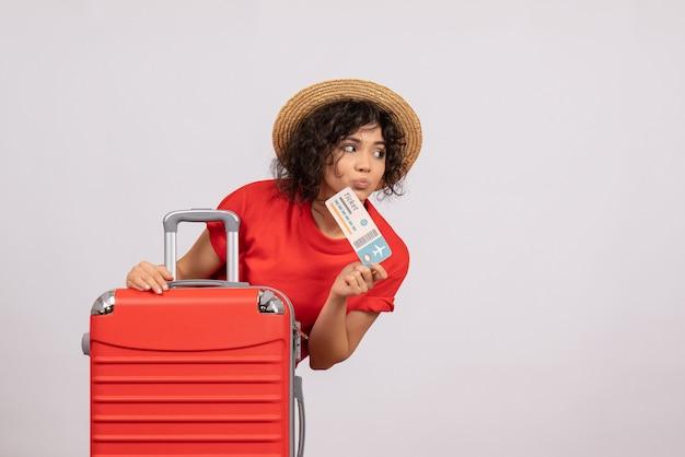 Vue de face jeune femme avec sac se préparant au voyage tenant un billet sur fond blanc couleur soleil voyage vacances repos vols avion
