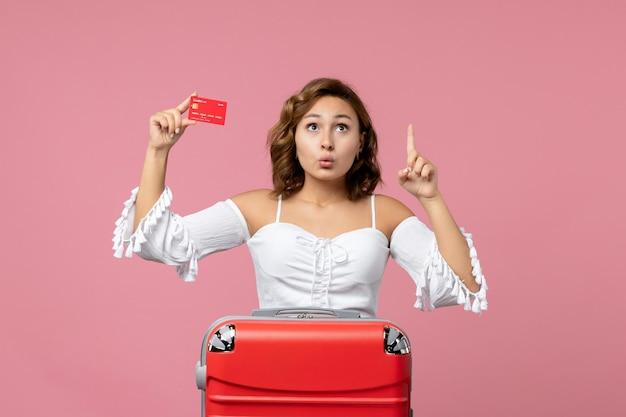 Vue de face d'une jeune femme avec un sac de vacances tenant une carte bancaire sur le mur rose