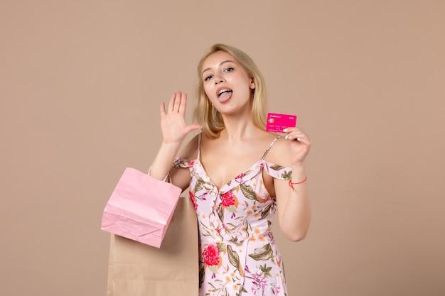 Vue de face d'une jeune femme avec des sacs à provisions et une carte bancaire sur un mur marron