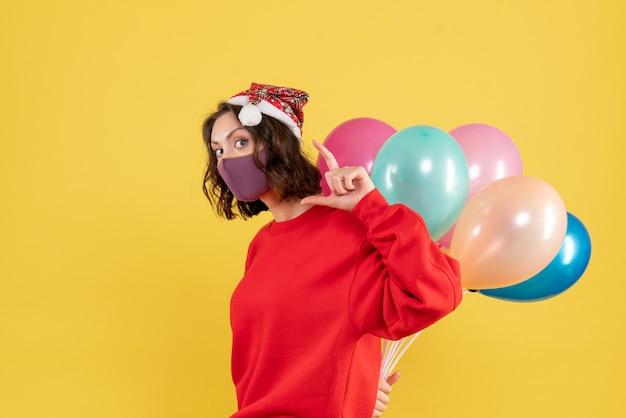 Vue de face jeune femme se cachant des ballons dans un masque stérile couleur vacances émotion nouvelle année noël femme