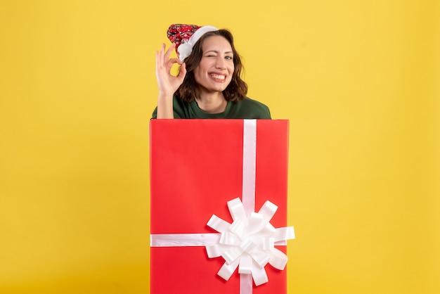 Vue de face jeune femme se cachant à l'intérieur de la boîte présente sur jaune