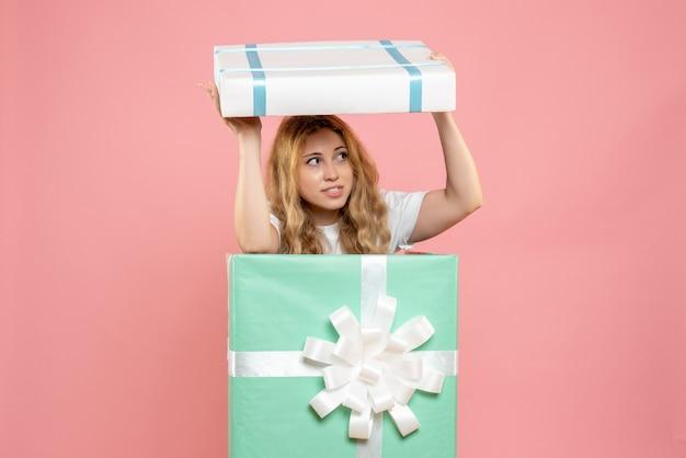 Vue de face jeune femme se cachant à l'intérieur de la boîte présente