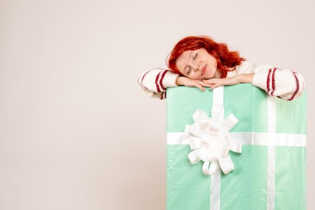 Vue de face de la jeune femme se cachant à l'intérieur du cadeau de noël dormir sur un mur blanc