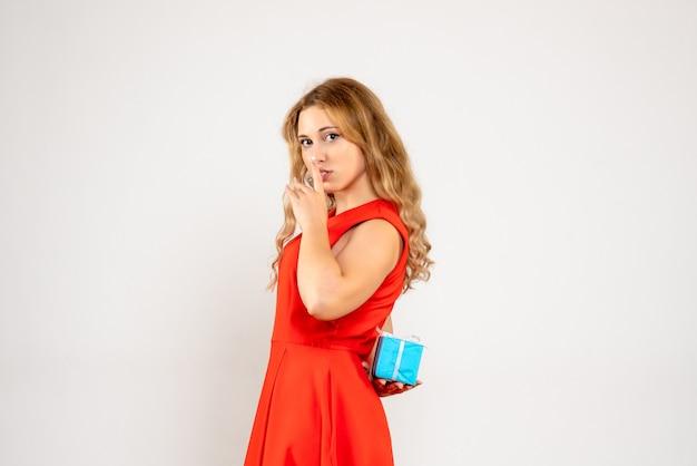 Vue de face jeune femme se cachant peu de cadeau de noël derrière son dos