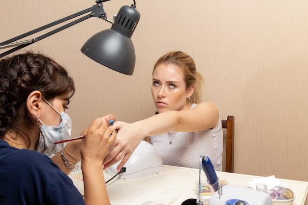Vue de face jeune femme se faire réparer les ongles par manucure à l'intérieur de la salle de cosmétologie beauté dame fille manucure ongles mode de soins personnels