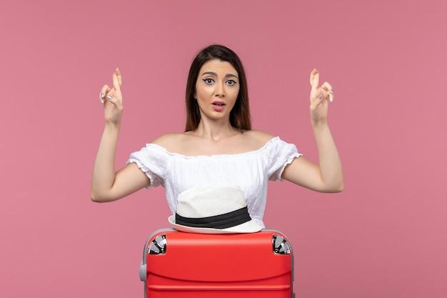 Vue de face jeune femme se préparant pour les vacances et croisant ses doigts sur fond rose voyage voyage voyage à l'étranger voyage en mer