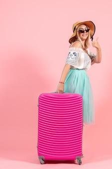 Vue de face jeune femme se préparant pour les vacances d'été avec un sac rose sur le fond rose couleur voyage voyage hydravion reste