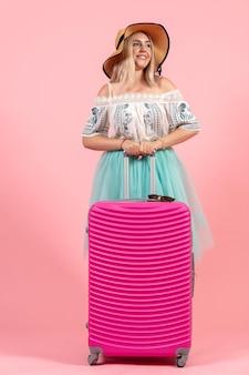 Vue de face jeune femme se préparant pour les vacances d'été avec un sac rose sur fond rose couleurs voyage voyage hydravion reste
