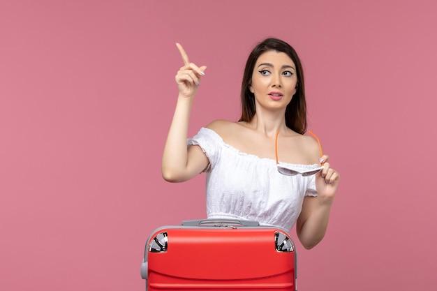 Vue de face jeune femme se préparant pour des vacances sur fond rose voyage voyage en mer voyage femme voyage à l'étranger