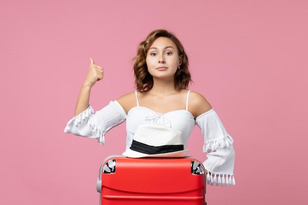 Vue de face d'une jeune femme se préparant pour des vacances avec un sac rouge posant sur le mur rose