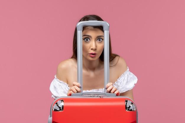 Vue de face jeune femme se préparant pour les vacances avec son gros sac sur fond rose voyage voyage à l'étranger voyage en mer
