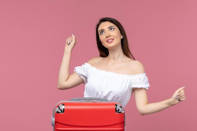 Vue de face jeune femme se préparant pour les vacances avec son gros sac tout en étant excité sur fond rose voyage voyage à l'étranger voyage en mer