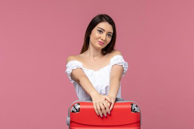 Vue de face jeune femme se préparant pour des vacances avec son gros sac tout en étant heureux sur fond rose voyage voyage à l'étranger voyage en mer