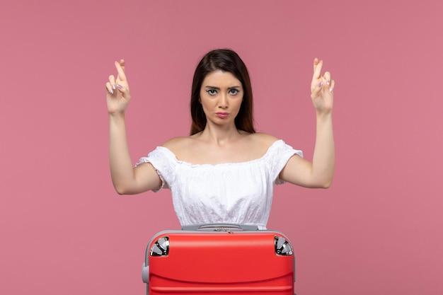 Vue de face jeune femme se préparant pour les vacances avec son sac croisant les doigts sur fond rose voyage à l'étranger voyage en mer voyage voyage