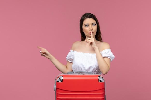 Vue de face jeune femme se préparant pour les vacances avec son sac rouge sur fond rose voyage à l'étranger voyage en mer voyage voyage