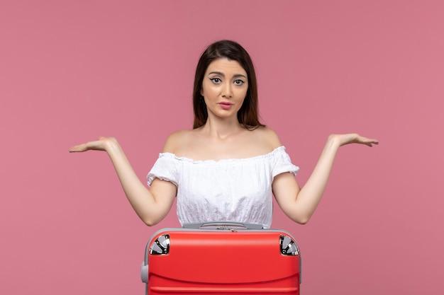 Vue de face jeune femme se préparant pour les vacances avec son sac rouge sur le fond rose voyage voyage à l'étranger voyage en mer
