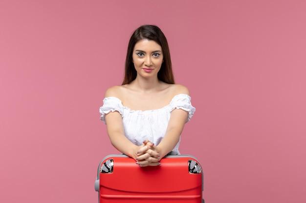 Vue de face jeune femme se préparant pour les vacances avec son sac rouge sur un fond rose voyage voyage en mer femme vacances à l'étranger