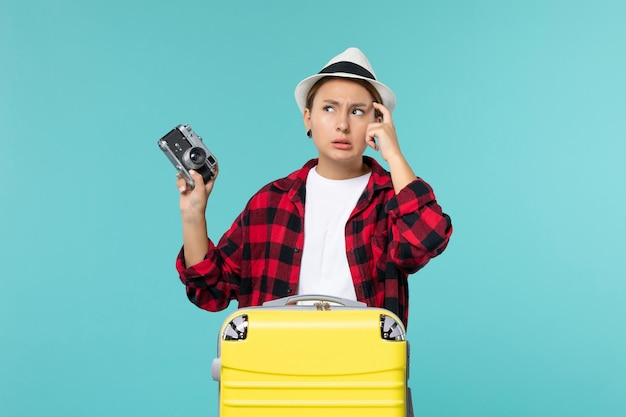 Vue de face jeune femme se préparant pour les vacances et tenant un appareil photo sur l'espace bleu