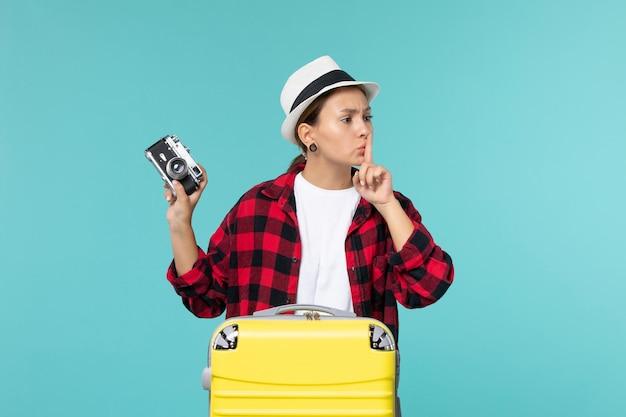 Vue de face jeune femme se préparant pour les vacances et tenant la caméra sur l'espace bleu