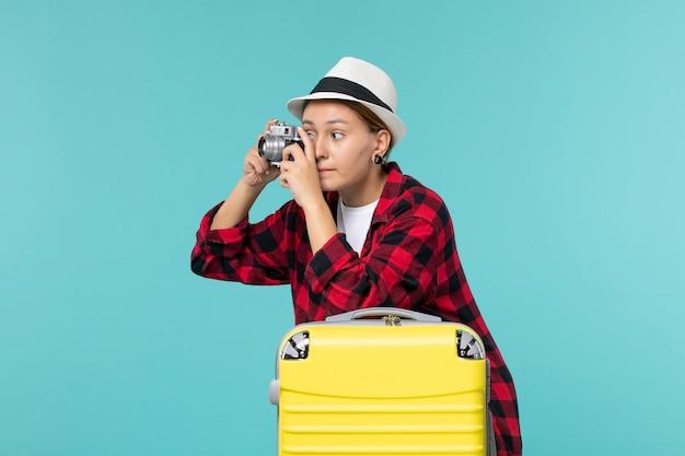Vue de face jeune femme se préparant pour les vacances tenant la caméra et prenant la photo sur l'espace bleu