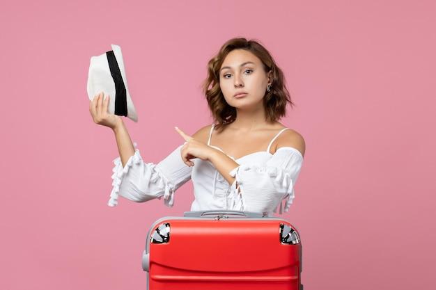 Vue de face d'une jeune femme se préparant pour les vacances et tenant un chapeau sur le mur rose