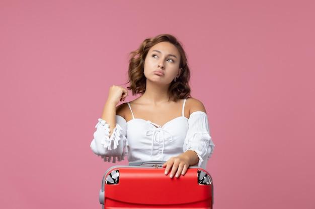 Vue de face d'une jeune femme se préparant pour un voyage avec un sac rouge sur le mur rose