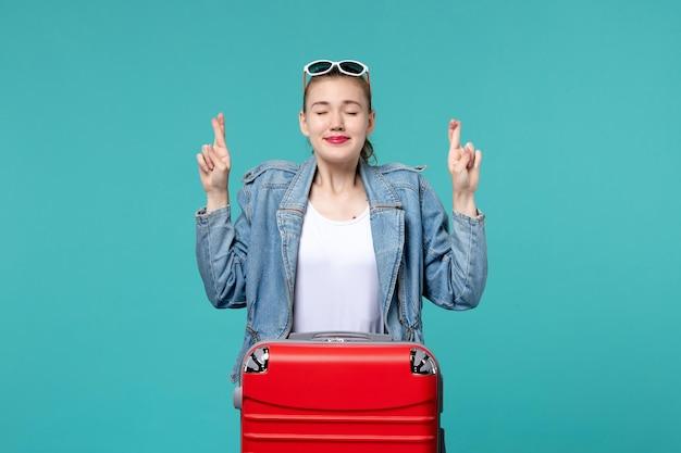 Vue de face jeune femme se prépare pour le voyage en croisant ses doigts sur l'espace bleu