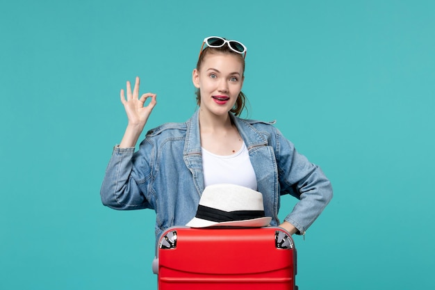 Vue de face jeune femme se prépare pour le voyage avec sac rouge et chapeau sur l'espace bleu