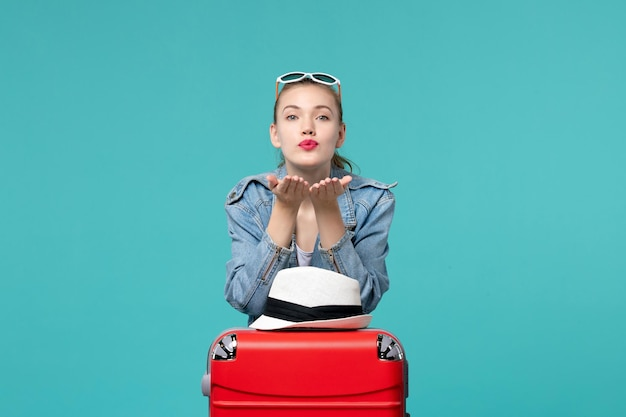 Vue de face jeune femme se prépare pour le voyage avec un sac rouge sur l'espace bleu