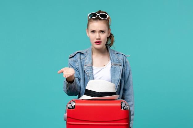 Vue de face jeune femme se prépare pour le voyage avec son sac rouge sur l'espace bleu