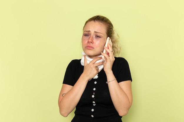 Vue de face jeune femme se sentant très malade et malade de parler au téléphone sur le mur vert maladie médecine féminine maladie